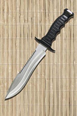 Fixed Blade Tactical Combat Hunting Survival Sawback Bowie Knife Set On Slatted Rustic Bamboo Place Mat Background