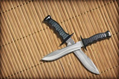 Tactical Combat Hunting Survival Bowie Knives With Crossed Blades On Slatted Rustic Bamboo Place Mat Vignette Background