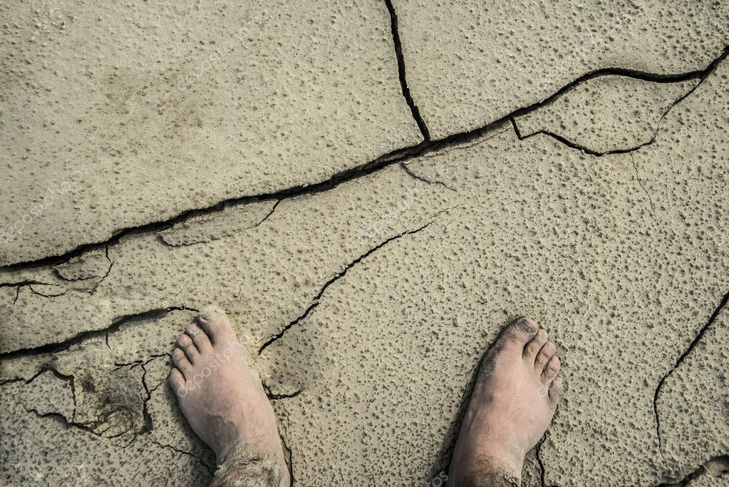 feet on dry cracked ground