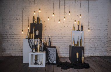 Candles in bottles on white and black cubes