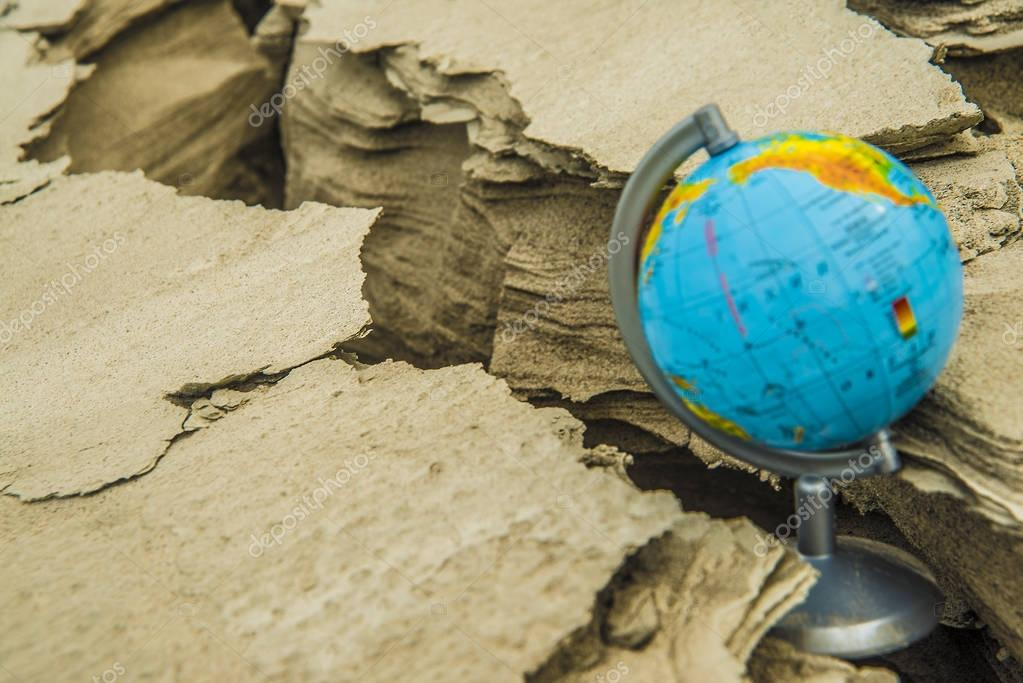 globe  stands in cracked soil.
