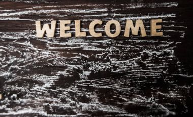 word - welcome on wooden table