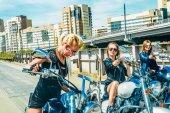 Fotografia Tre giovani ragazze su elicotteri contro metallo ponte sfondo biondo femmina