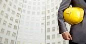 inženýr se žlutou helmu pro bezpečnost pracovníků na pozadí nové budovy