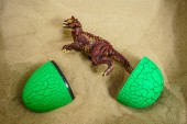 dinosaur hatched from green egg on sand background.