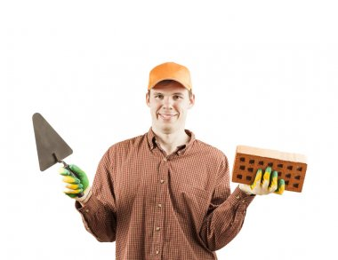 portrait of young adult happy mason  in a red plaid shirt holding red brick with holes and black trowel on gray background