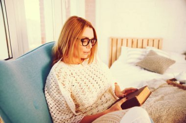 Young blond woman at home sitting on modern chair in front of window relaxing in her living room reading book