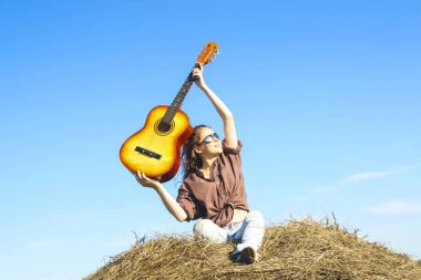 Country girl holding  guitar at haystack.