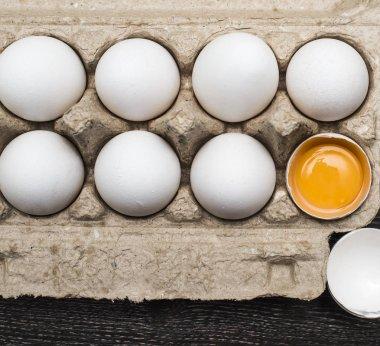 Eggs in egg tray, one egg  cracked. Group of white fresh eggs stock vector