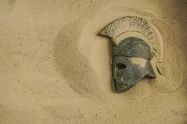 helmet of ancient warrior in sand. Roman  helmet with the Iroquois. Archaeology and paleontology concept