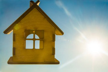 wooden house toy against blue sunny sky with sun rays