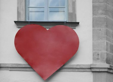 one big red heart hang under white window frame on yellow wall background. yellow european house. empty frame for menu. st. Valentines day. 14th February.