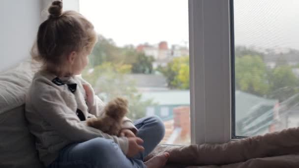 Junges Mädchen schaut aus dem Fenster auf der Fensterbank sitzend