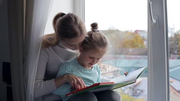 Mladá matka s dcerou čtení knihy u okna