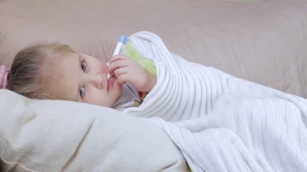Ein krankes junge Mädchen mit einem Thermometer. Krankes Kind-Konzept