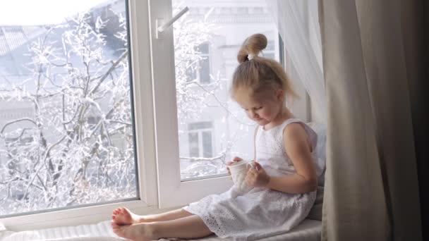 Nettes kleines Mädchen trinkt Tee sitzend auf der Fensterbank. sonniger Wintermorgen