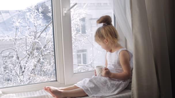 Roztomilá holčička s šálkem čaje sedí na okenním parapetu. Dívka s cup do oken. Slunečné zimní ráno
