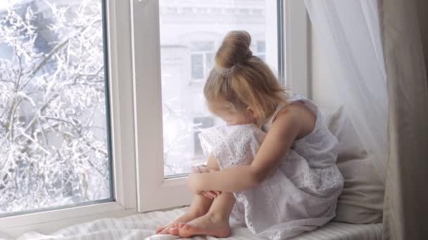 Smutný holčička se dívá oknem sedí na okenním parapetu. Zima mimo