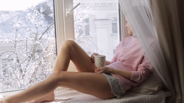 Mladá žena s horký šálek čaje ot sedí na okenním parapetu. Zimní