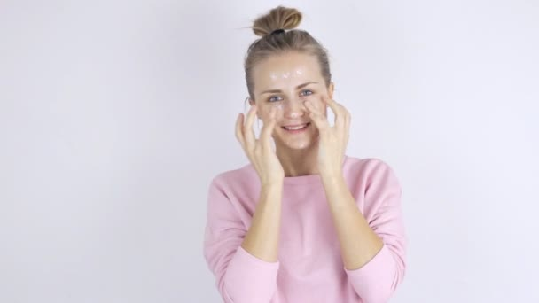 Young beautiful woman applying cream on her face. Skincare concept