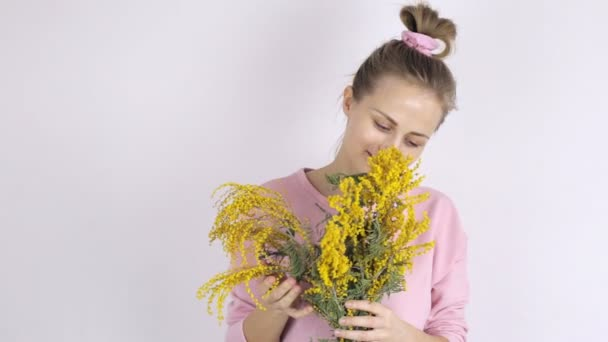 Young cute woman with yellow mimosa flowers