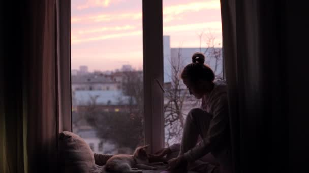 Mädchen mit Katze sitzt frühmorgens auf Fensterbank