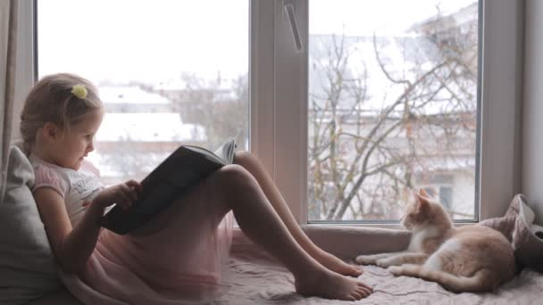 Děvčátko, které čte knihu, sedí na parapetu.