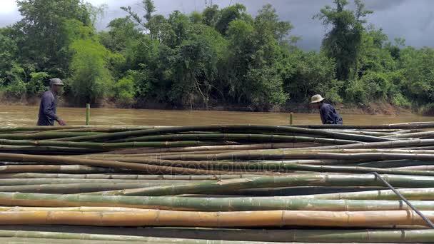 Dělníci stohování stejné velikosti bambusové tyče nahoru ve vodě podél řeky