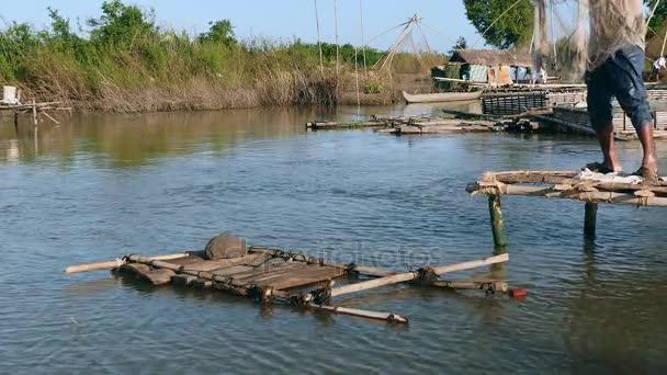 Detailní záběr na fisher casting net do rybníka z malé dřevěné platformy.