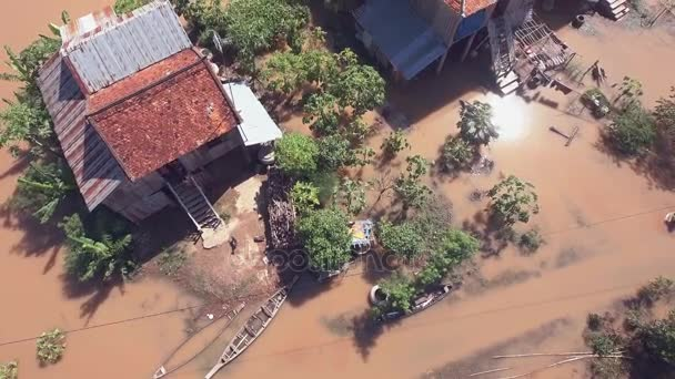 Aerial : fly up over two families walking through flooded yard leading to their rural houses