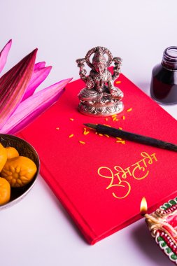 An auspicious Indian writing Shubha Labh means 'Goodness' & 'Wealth', over Red accounting note book / 'bahi khata' with goddess Laxmi, diya, sweets and lotus and pen with ink on laxmi pujan, on diwali