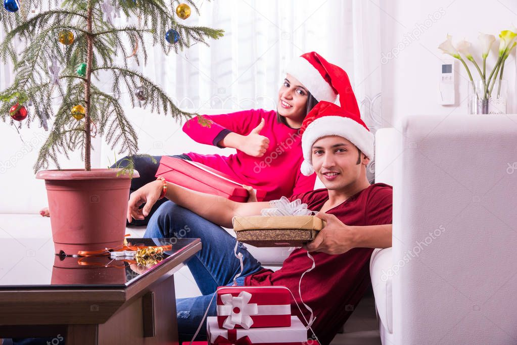 merry christmas young indian or asian couple celebrating christmas at home with surprise gift boxes