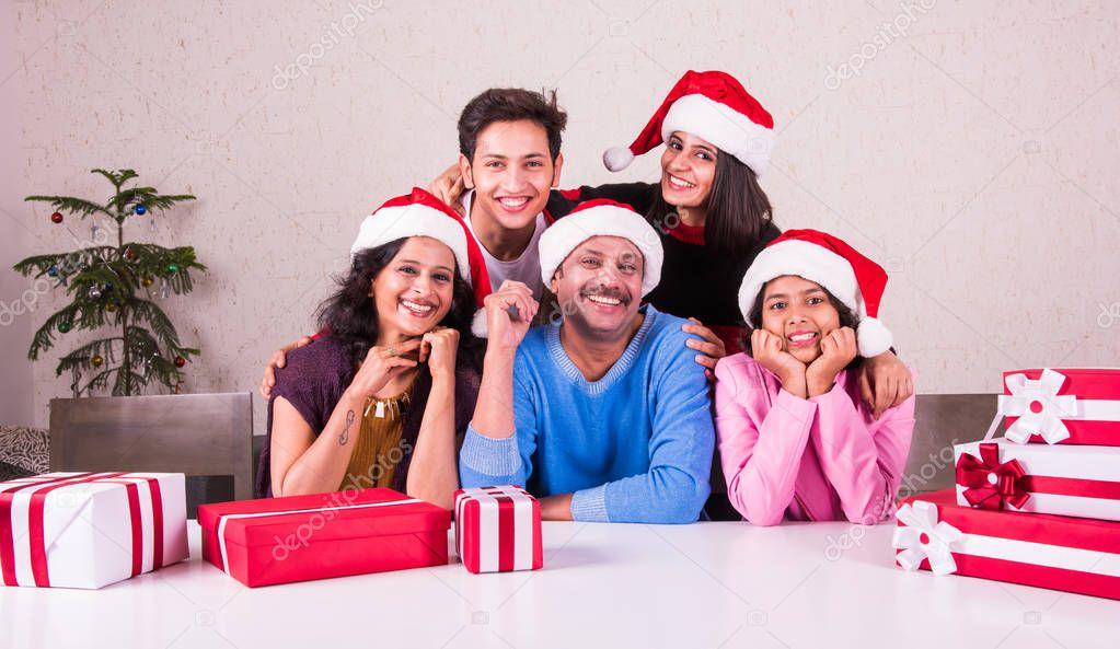 Weihnachtszeit, glückliche indische Familie sitzen über Tisch mit ...