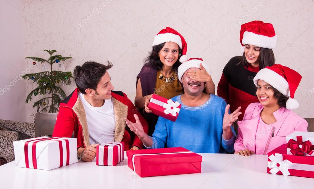 Christmas time, Happy indian family sitting across table and