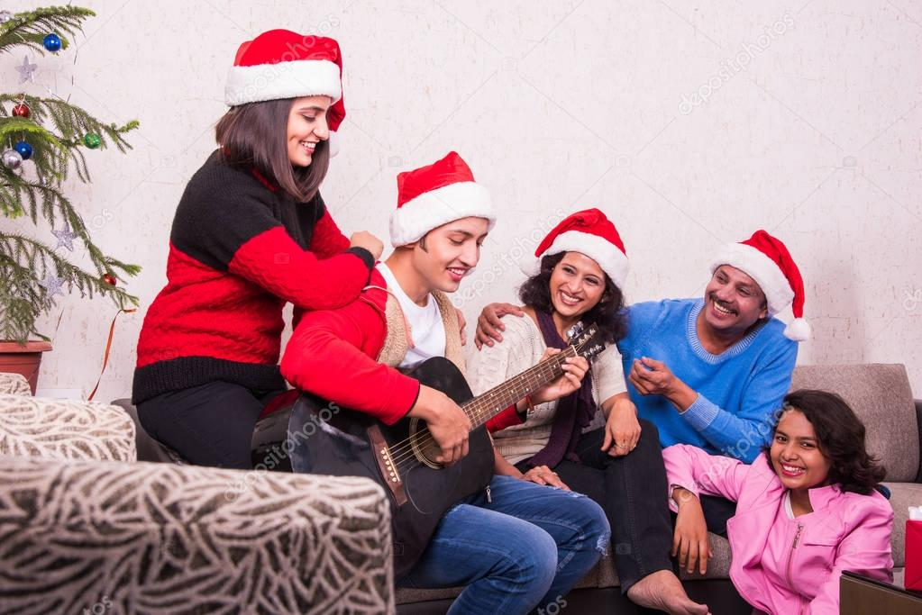 family christmas holidays and people concept happy indian family sitting on sofa and boy playing song on guitar indian family celebrating christmas