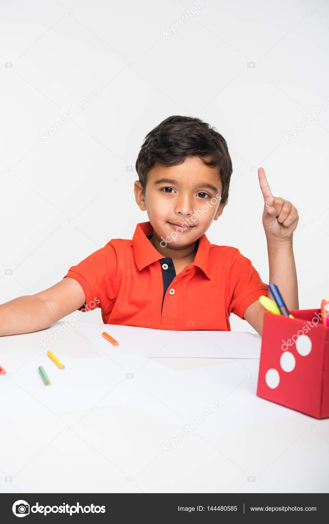enfant gar on indien l aide de crayon de couleur pour le dessin assis table blanche. Black Bedroom Furniture Sets. Home Design Ideas