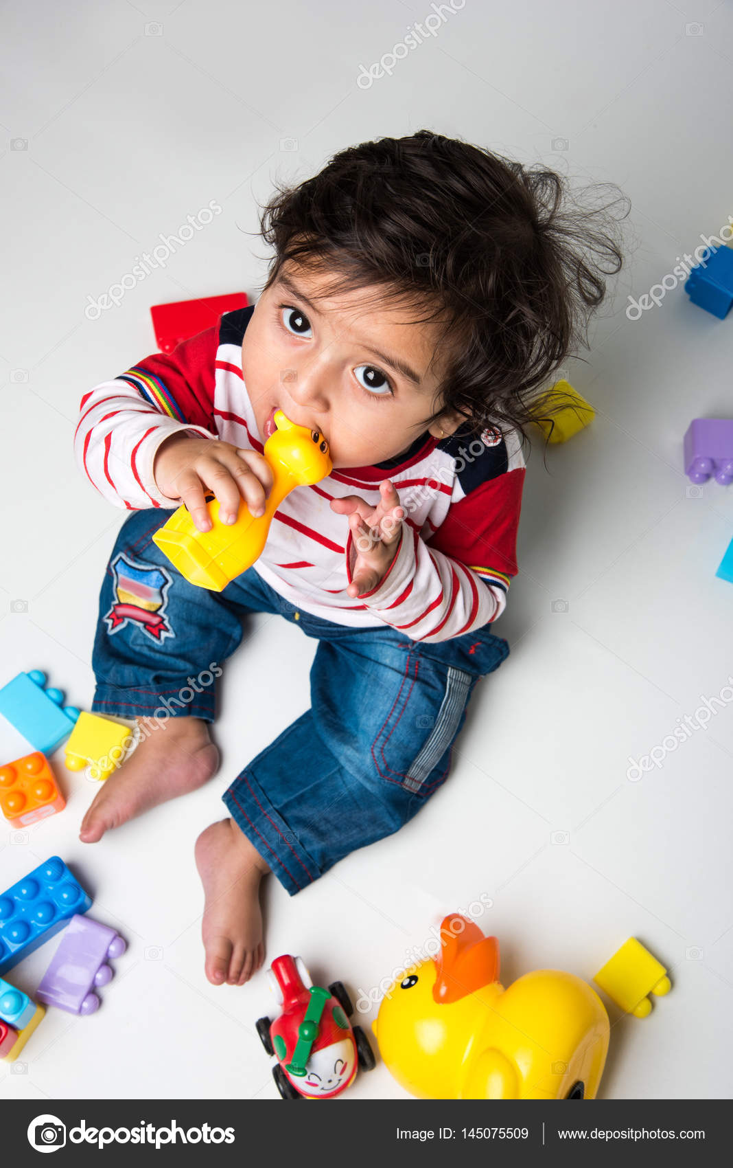 indian or asian small baby playing with toys or blocks over white