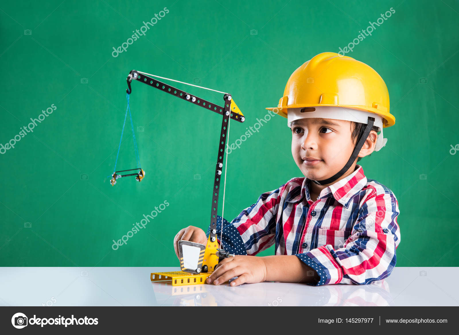 Cute indian baby boy playing with toy crane wearing yellow construction hat  or hard hat a2c7dd850b6