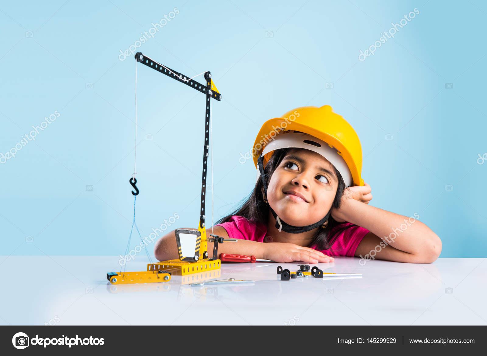Neonata indiana carina che gioca con gru giocattolo indossando cappello  giallo costruzione o concetto duro di cappello 249dfc3b85cf