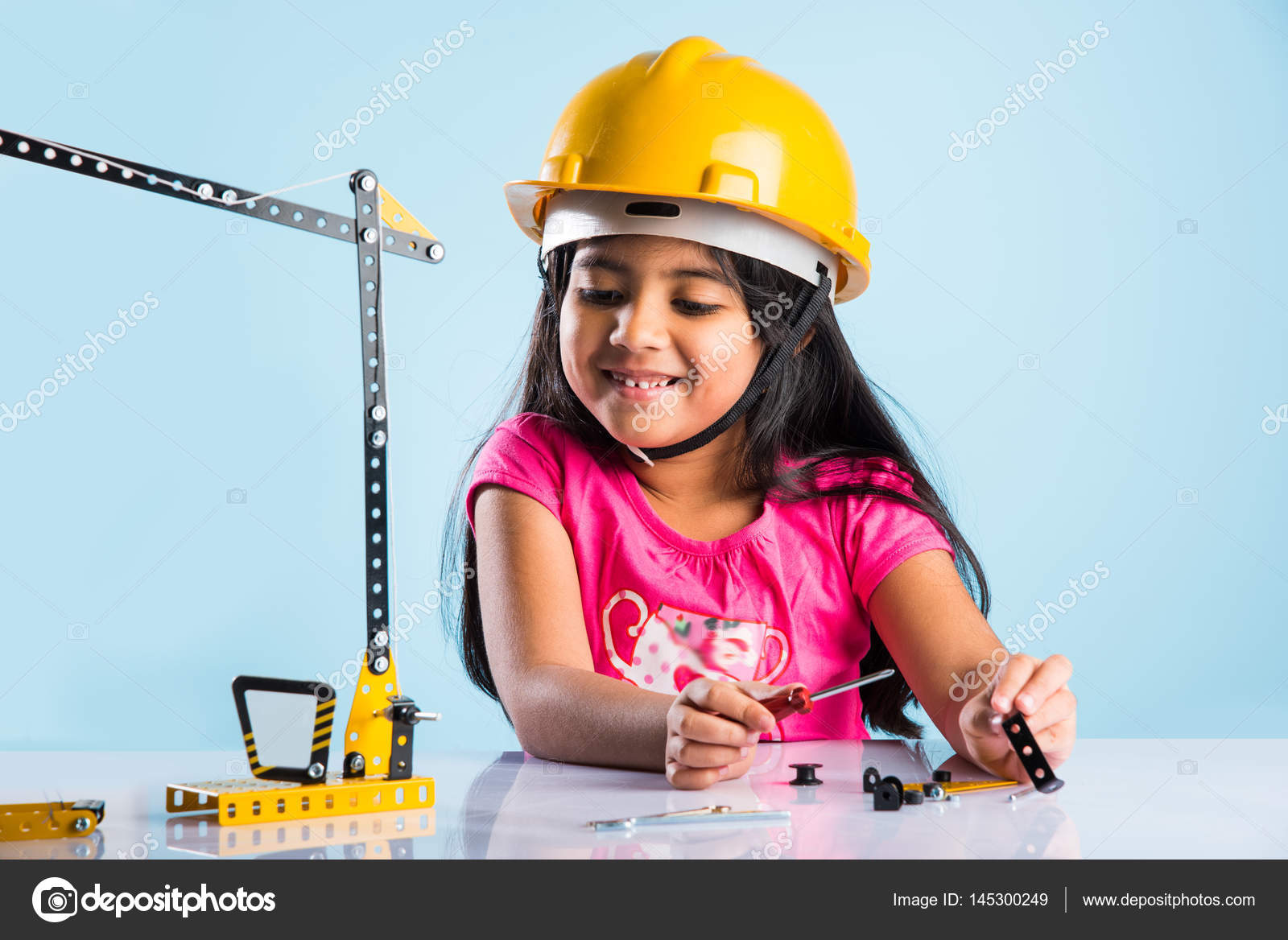cute indian baby girl playing with toy crane wearing yellow