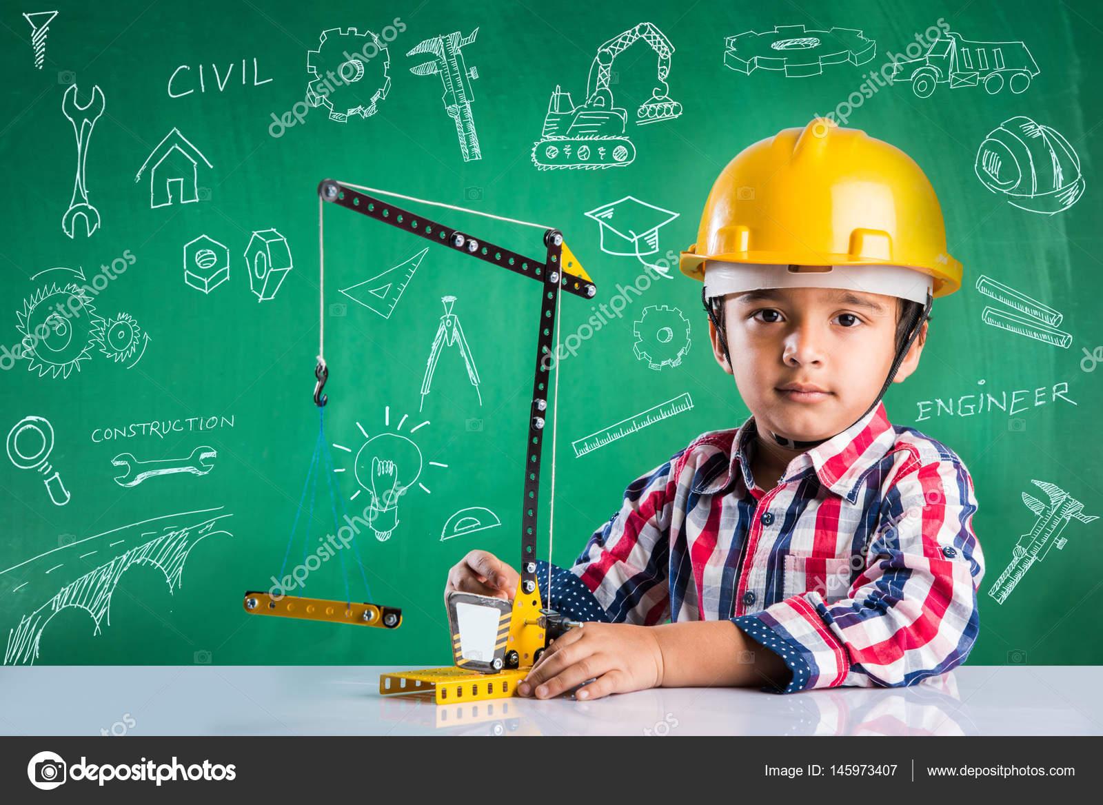 Neonato indiano sveglio che gioca con la gru giocattolo indossando cappello  giallo costruzione o concetto duro di cappello fd761621e04c