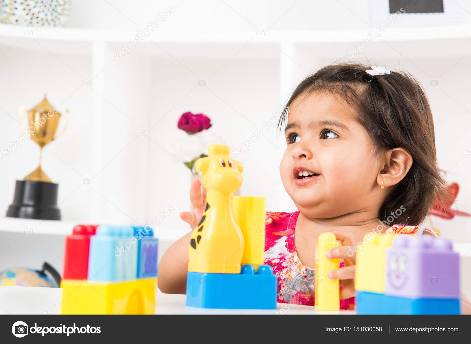 indian cute and happy baby girl playing with toys over table — stock