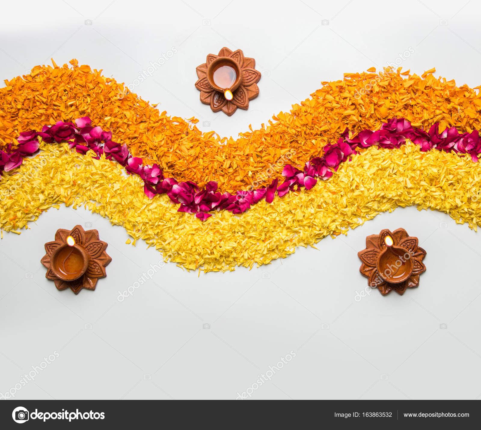 Flower Rangoli For Diwali Or Pongal Made Using Marigold Or Zendu Flowers And Red Rose Petals Over White Background With Diwali Diya In The Middle Selective Focus Stock Photo C Stockimagefactory Com