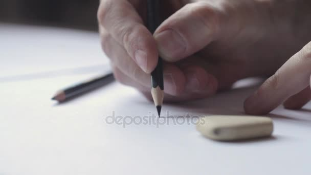 Close up of a male hand drawing with a black pencil