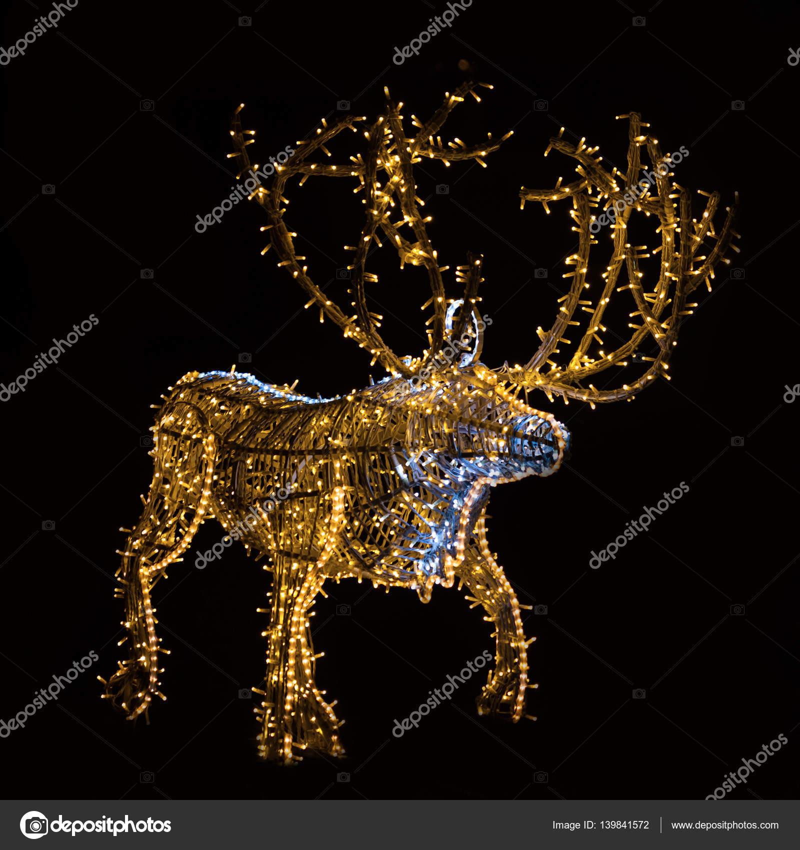 close up van een houten kerst rendier versierd met blauwe en gele led verlichting in de nacht donkere achtergrond foto van macondos