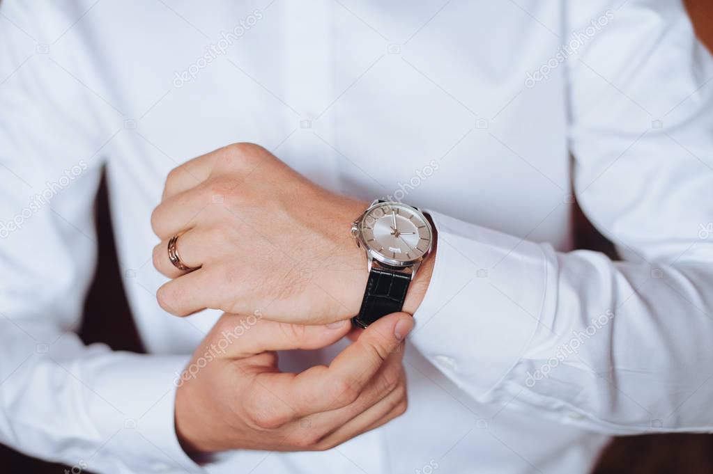 155d275b588a Ένας Άντρας Ένα Λευκό Πουκάμισο Θέση Σχετικά Ρολόι Του Γαμπρός — Φωτογραφία  Αρχείου © Shchus  178304770