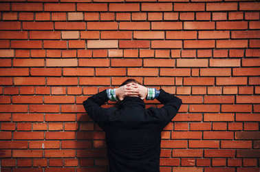 Bandit arrested and standing near a brick wall. The concept of crime and punishment.