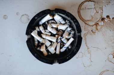 Closeup of ashtray with butts on dirty table