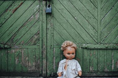 Old doll sitting in doorway. Old wooden shed. Fear, hate, horror, loneliness. Vintage
