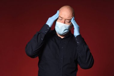 man with mask and latex gloves have headache on red background